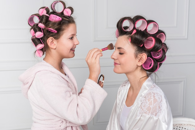 Daughter putting powder on mothers forehead Free Photo