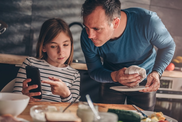 Daughter showing text message to a father Premium Photo