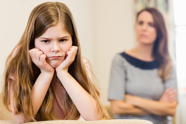 Daughter sitting upset with her mother in living room Free Photo