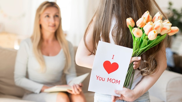 Daughter surprising mother with tulips Free Photo