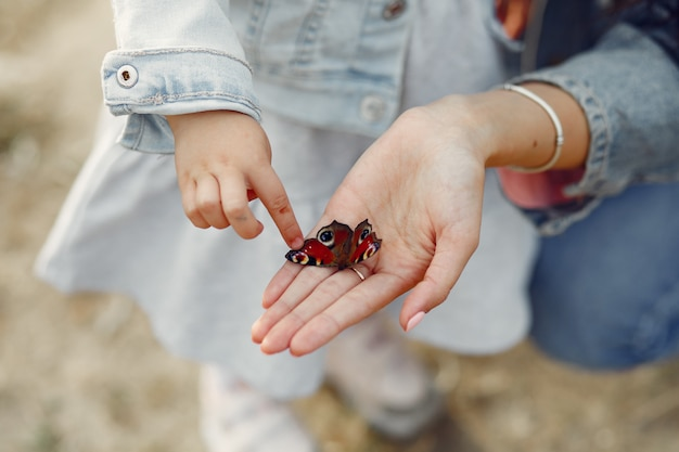 Daughter touching a butterfly Free Photo