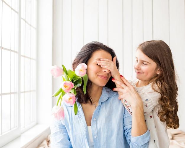 母の目を覆っている花を持つ娘 Premium写真