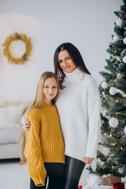 クリスマスツリーのそばで母親と娘 無料写真