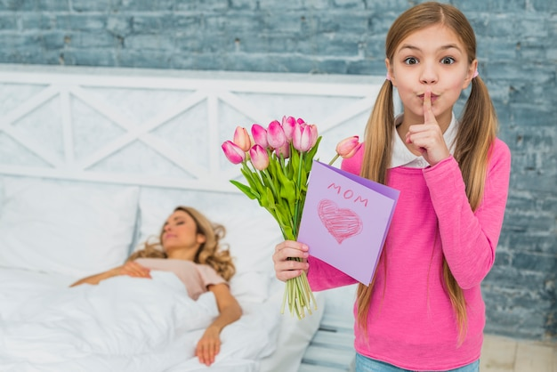 Daughter with tulips and greeting card holding finger on lips Free Photo