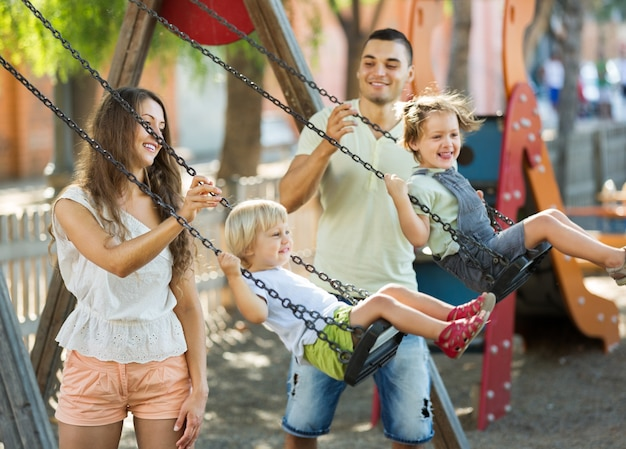 Daughters on swings with parents Free Photo