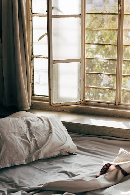 Daylight shining through an unmade bed Free Photo