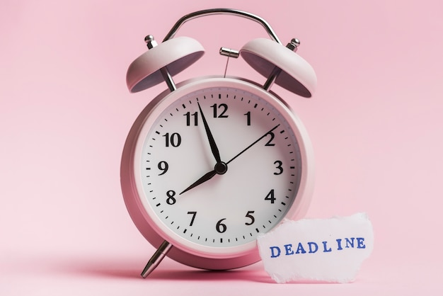 Deadline message on torn paper piece near the alarm clock against pink backdrop Free Photo