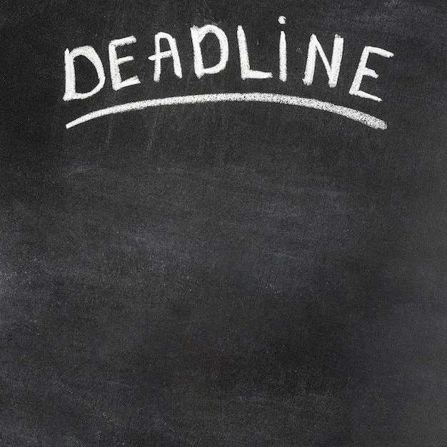 Deadline text written on black chalkboard with chalk Free Photo