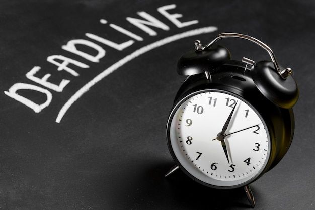 Deadline text written on chalkboard with alarm clock Free Photo