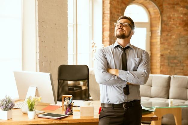 Сделки. молодой предприниматель, работающий в офисе, получает новое рабочее место. молодой офисный работник мужского пола при управлении после продвижения по службе. выглядит серьезно, уверенно. бизнес, образ жизни, новая концепция жизни. Бесплатные Фотографии