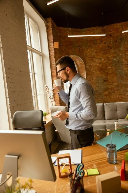 Offerte. un giovane imprenditore che lavora in ufficio Foto Gratuite