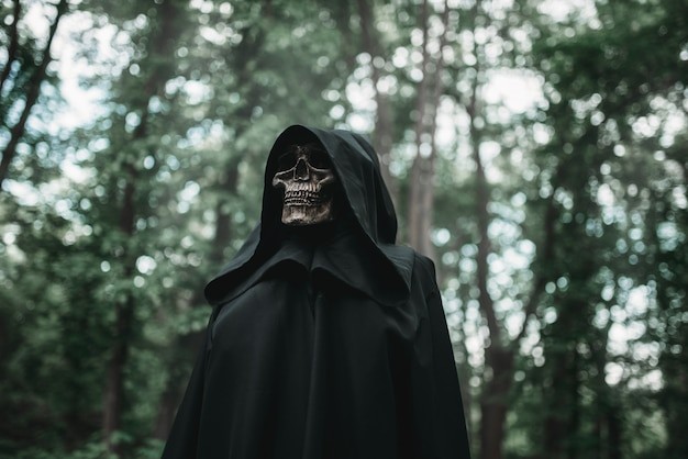Death in black hoodie in forest Premium Photo