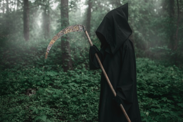 Death with a scythe in the dark misty forest Premium Photo