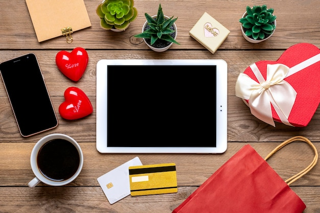 Debit card, chooses gifts, makes purchase, tablet, coffee cup, two hearts Premium Photo