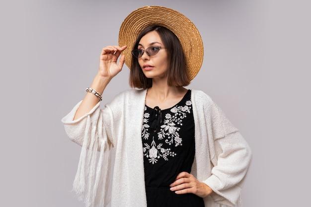 Жизнерадостная темноглазая девушка в соломенной шляпе и летнем наряде в стиле бохо позирует. Бесплатные Фотографии