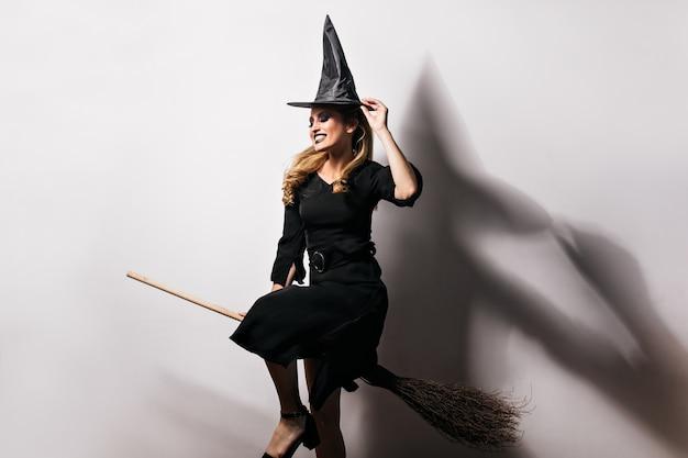 Девушка debonair в костюме ведьмы, наслаждаясь карнавалом. фото мечтательной светловолосой дамы, весело проводящей время в хэллоуин. Бесплатные Фотографии