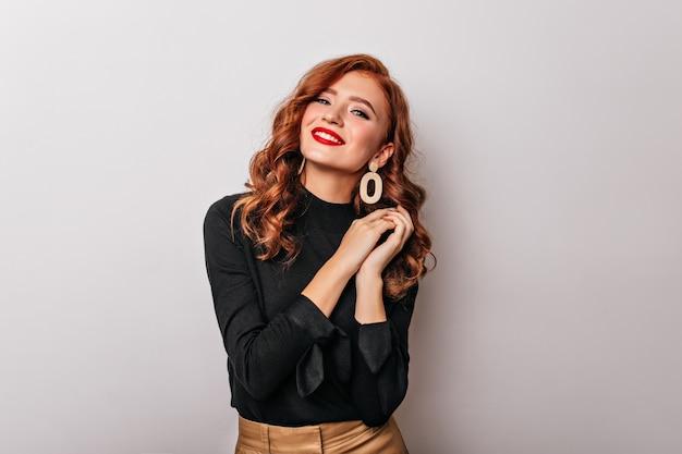 Donna alla moda debonair in camicetta nera sorridente. graziosa ragazza europea indossa orecchini d'oro. Foto Gratuite