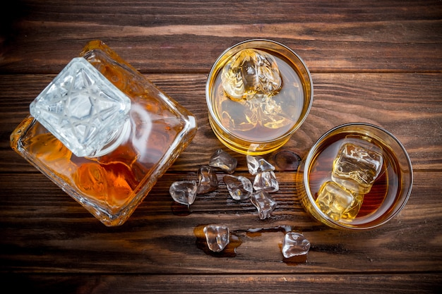 Decander and two glasses with ice and whiskey Premium Photo