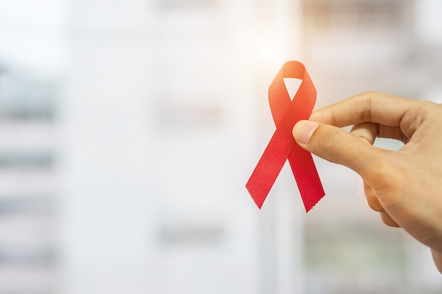 December world aids day awareness month, man holding red ribbon Premium Photo