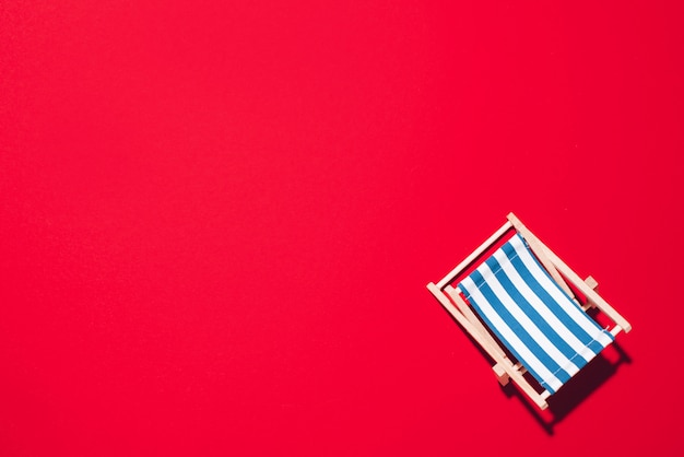 Deck chair with hard shadow on red paper background. Premium Photo