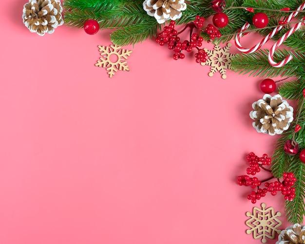 Decor - christmas tree branch, rowan, cone, lollipop, snowflake on pink background flat lay Premium Photo