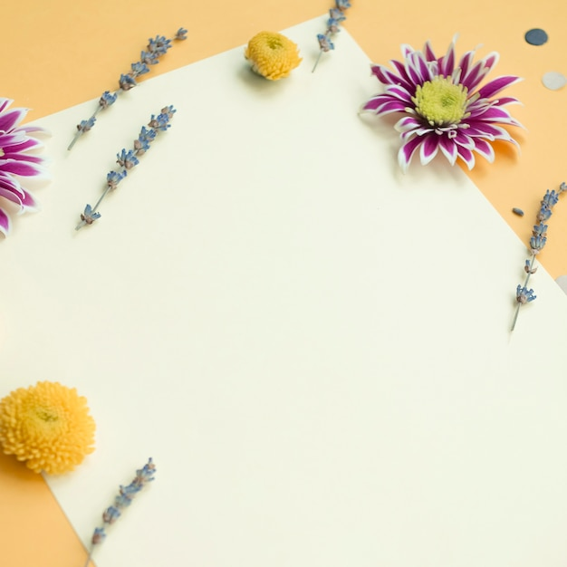 Decorated blank card with flowers over the yellow backdrop Free Photo