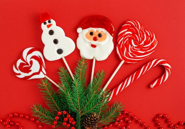Украшенные рождественские конфеты на красном фоне Premium Фотографии