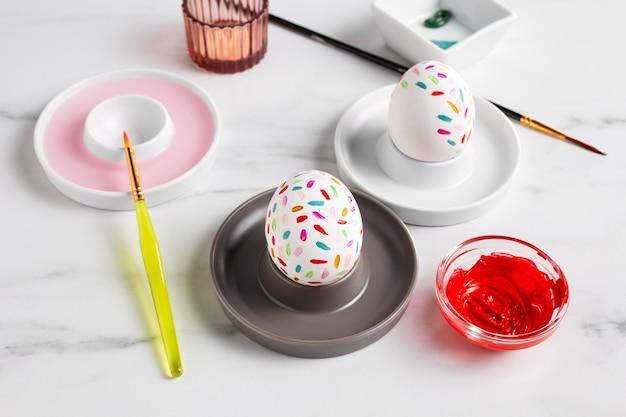 Украшенное пасхальное яйцо на тарелке краской и кистью Бесплатные Фотографии