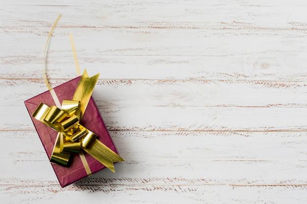 織り目加工の白い木製の表面にゴールデンリボンで飾られたギフトボックス 無料写真