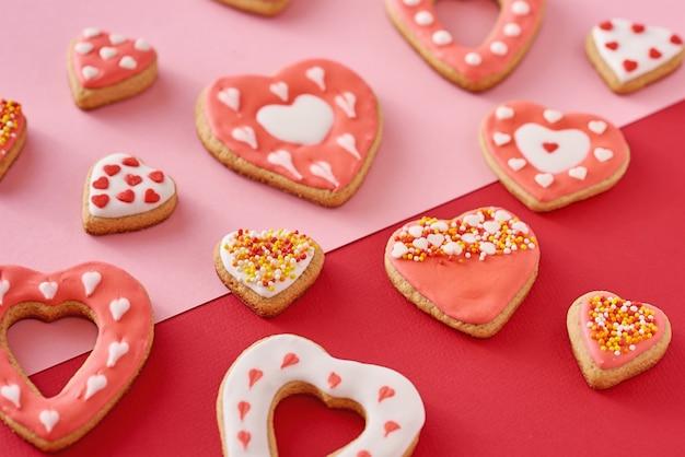 Украшенное печенье в форме сердца на красном и розовом Premium Фотографии