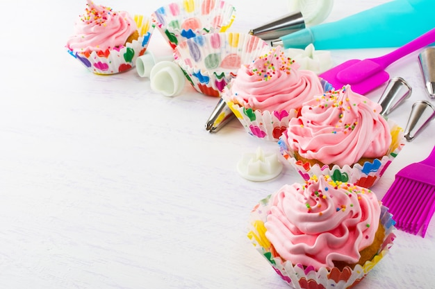 Decorated pink birthday cupcakes  and cookware Premium Photo