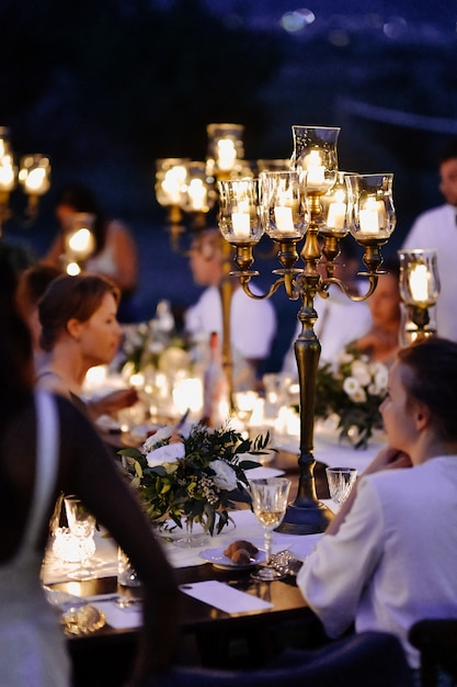 Tavoli decorati con composizione floreale e candelabri vecchio stile e ospiti nella serata di celebrazione Foto Gratuite