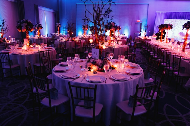 Decorated wedding hall with candles, round tables and centerpieces Free Photo