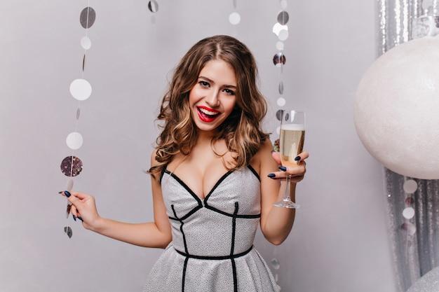 Украшенная елочными игрушками, юная леди улыбается и веселится, в красивом праздничном платье и держит бокал игристого вина в левой руке Бесплатные Фотографии