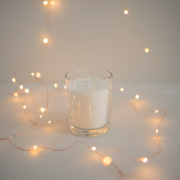 Decoration of fairy lights around glass candleholder Free Photo