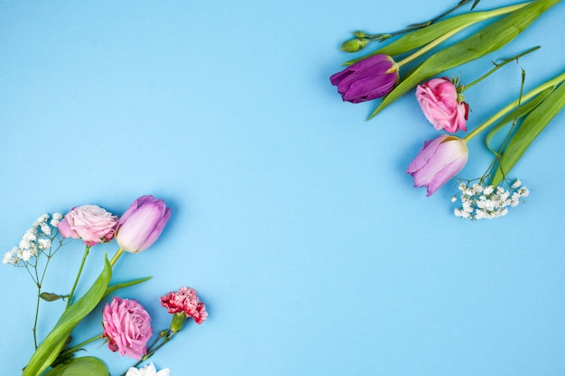 Decoration made from variety flowers against blue backdrop Free Photo