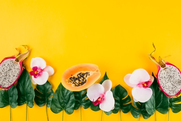 Decoration made with papaya; dragon fruits; orchid and artificial leaves on yellow background Free Photo