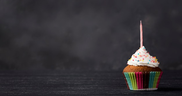 Decoration with muffin and candle on wooden background Free Photo