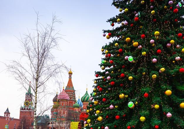 年末年始のデコレーション。モスクワの赤の広場の聖ワシリイ大聖堂の近くの木の枝にクリスマスボール Premium写真