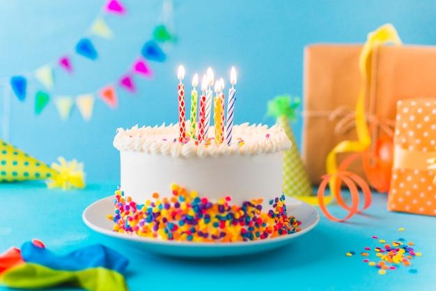 Декоративный торт с горящей свечой на синем фоне Premium Фотографии
