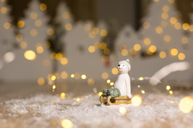 Decorative christmas-themed figurines. the statuette of a polar bear sits on a wooden sled, in a knitted hat and socks. Premium Photo