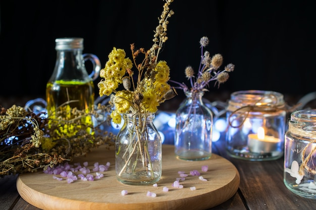 Decorative composition with dried herbs in small glass bottles Premium Photo