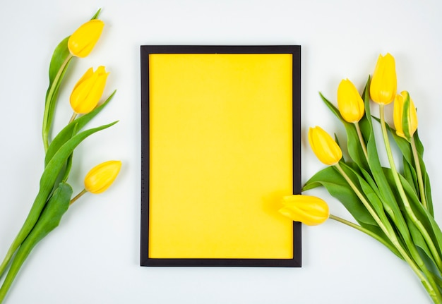 Decorative empty frame with copy space and bouquet of tulips Premium Photo