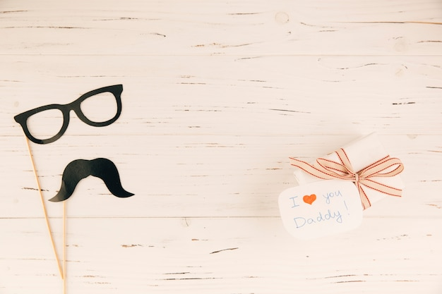 Decorative eyeglasses and moustache near present Free Photo