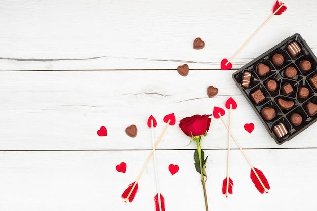 Piume decorative su bacchette con cuoricini vicino a fiori e dolci Foto Gratuite