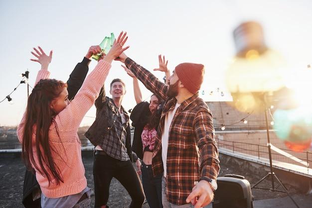 장식 축제 전구. 옥상 휴일. 친구의 쾌활한 그룹은 알코올로 손을 올렸다 무료 사진