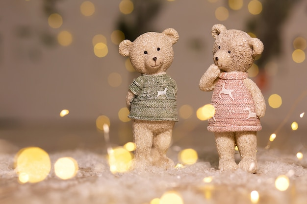 Decorative figurines of a christmas theme. figurines of cute teddy bears of a boy and a girl in sweaters with deers. festive decor, warm bokeh lights. Premium Photo