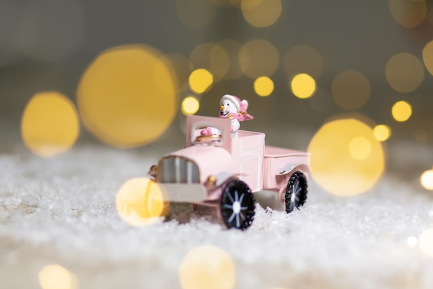 Decorative figurines of a christmas theme. santa statuette rides on a toy car with a trailer for gifts. Premium Photo