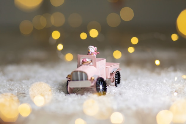 Decorative figurines of a christmas theme, santa statuette rides on a toy car with a trailer for gifts, , Premium Photo