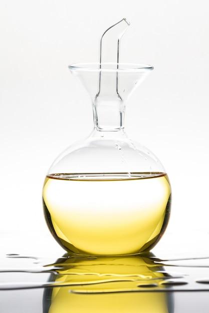 白のオリーブオイルと装飾的なガラスの瓶。 Premium写真